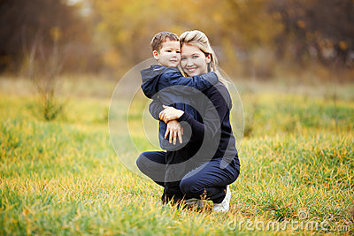 Young mother and son in autumn forest park, yellow foliage. Casual wear. Kid wearing blue jacket. Incomplete family