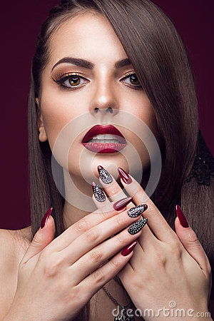 Pretty girl with unusual hairstyle, bright makeup, red lips and manicure design. Beauty face. Art nails