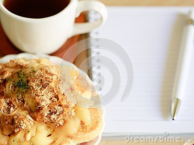 Danish pastry with a cup of hot tea and a pen and small notebook on wood table in morning time