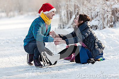 Happy couple having fun ice skating on rink outdoors