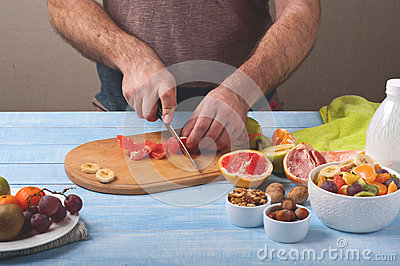 Male on a kitchen table preparing fruit salad