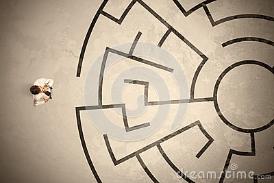 Lost business man looking for a way in circular labyrinth