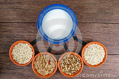 Four small bowls with different cereals and bowl with milk, business strategy, decision making, choice.