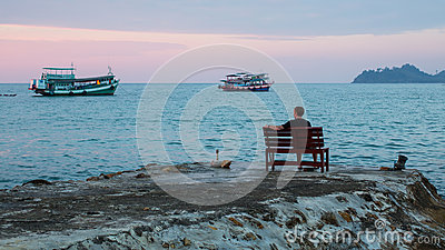 Lonely man sits on a bench on the coast watching the fishing boats