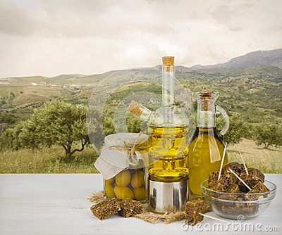 Olive oil and black bread over trees of olives background