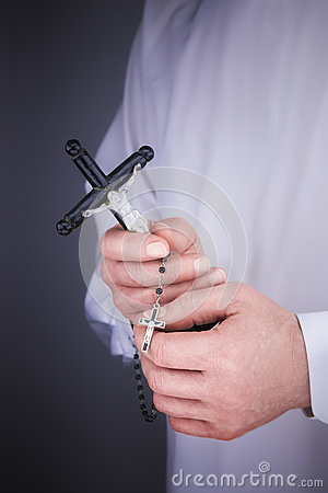 Man's hands with a white cape, crucifix and a black rosary