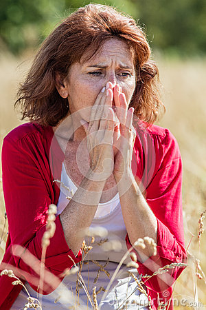 50s woman sneezing for rhinitis,allergies or hay fever