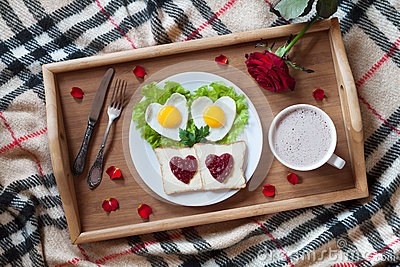 Breakfast in bed with heart-shaped eggs, toasts, jam, coffee, rose and petals. Valentines Day surprise.