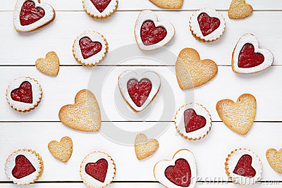 Heart shaped and shortbread cookies with jam gift composition for Valentines Day on vintage wooden background.