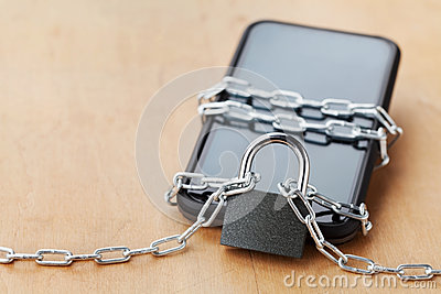 Smartphone tied chain with lock on wooden table, gadget and digital devices detox concept