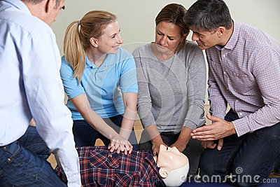 Woman Demonstrating CPR On Training Dummy In First Aid Class