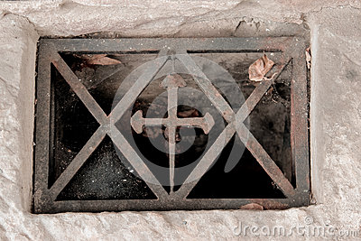 The window in the basement with a cross in metal frame with cobwebs in the corners, metal, rusty, scratched, dirty, dark bottom.
