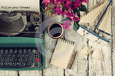 stock image of image of vintage typewriter with phrase follow your dreams, blank notebook, cup of coffee and old sailboat