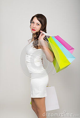 Beautiful young lady in a little white dress on high heels, holding colorful bags. Girl goes shopping