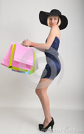 Beautiful young lady in a little blue dress on high heels, holding colorful bags. Girl goes shopping