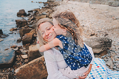 portrait of happy mother and daughter spending time together on the beach on summer vacation. Happy family traveling, cozy mood.