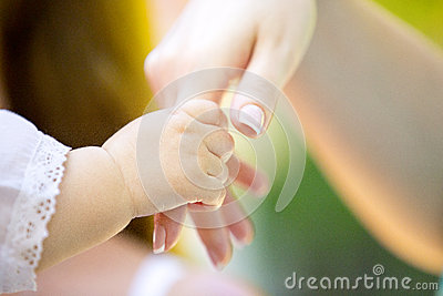 Tiny baby's hand and hand of adult