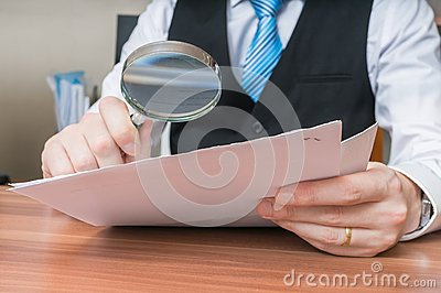Laywer is analysing document with magnifying glass