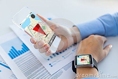 Hands with navigator map on smart phone and watch