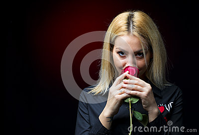 Portrait of a beautiful blonde girl smelling a red rose