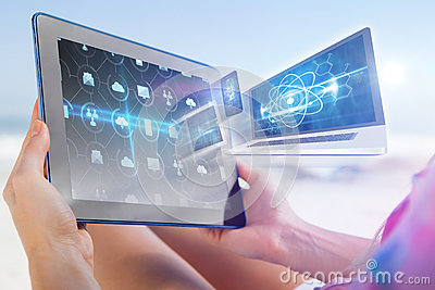 Composite image of woman sitting on beach in deck chair using tablet pc