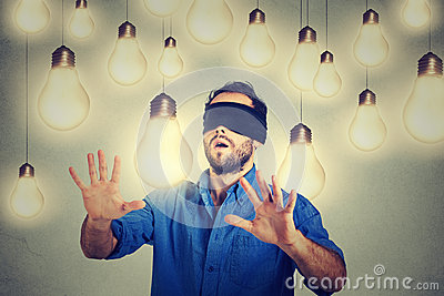 Blindfolded man walking through light bulbs searching for bright idea