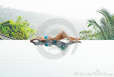 Attractive, young woman in cyan swimsuit lying poolside