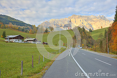 View of a country road passing by a farm land with a church on top of the hill and Mountain Hochkoenig