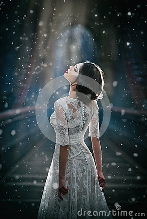Lovely young lady wearing elegant white dress enjoying the beams of celestial light and snowflakes falling on her face