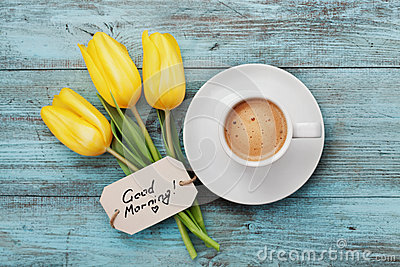 Coffee mug with yellow tulip flowers and notes good morning on blue rustic table from above
