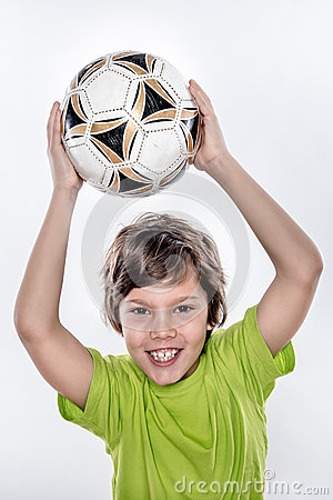 Cute Smiling Soccer Kid Holding Ball above His Head