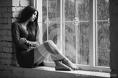 Beautiful young woman sitting alone close to window with rain drops. and sad girl. Concept of loneliness. Black