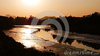 Romantic orange sunset with small curve river and tree reflectio