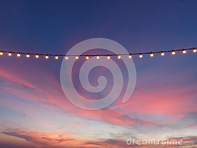 Light bulbs on string wire against sunset sky