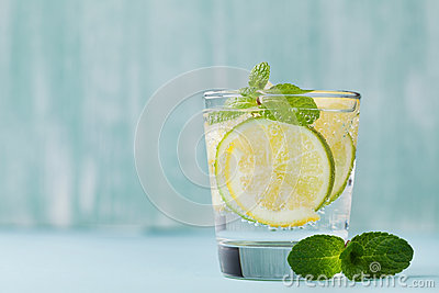 Mineral infused water with limes, lemons, ice and mint leaves on blue background, homemade detox soda water
