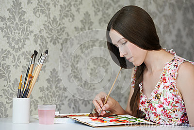Young woman painter drawing watercolor poppies at her home studio