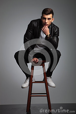 Young male in black posing seated on stool in studio