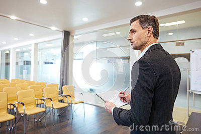 Businessman with clipboard standing in empty conference hall