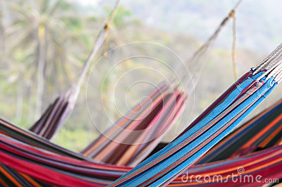 Many colorful hammocks hanging behind each other