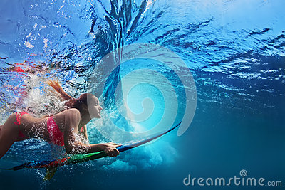 Underwater photo of surfer girl diving under ocean wave