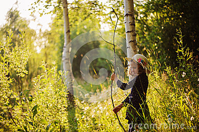 Dreamy child girl on summer walk on riverside. Cozy rural scene. Outdoor activities