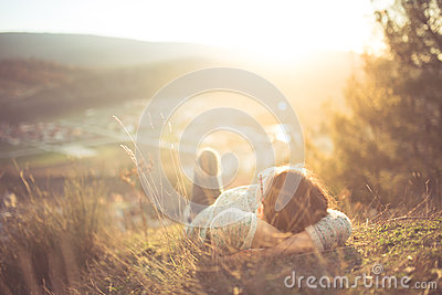 Carefree happy woman lying on green grass meadow on top of mountain edge cliff enjoying sun on her face. Enjoying nature sunset
