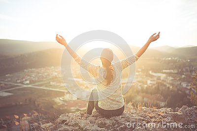 Carefree happy woman sitting on top of mountain edge cliff enjoying sun on her face raising hands in sunlight rays.Enjoying nature