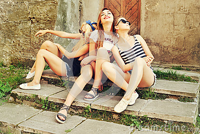 Three beautiful girls rest on the street. Beautiful happy girls in sunglasses on the urban background. Young active people. Outdoo