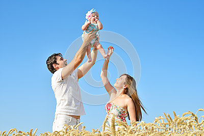 Family portrait. Picture of happy loving father, mother and their baby outdoors. Daddy, mom and child against summer blue sky.