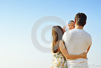 Family portrait. Picture of happy loving father, mother and their baby outdoors. Back view.