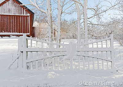 Snowy gate and red barn in the background a winter day
