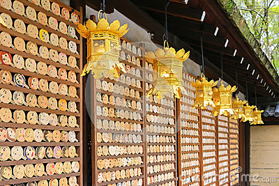 Golden lanterns hanging in front of mirror-shaped wooden preyer