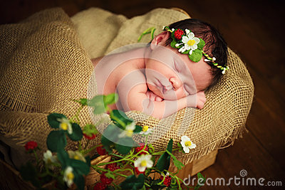 Newborn baby girl has sweet dreams in strawberries