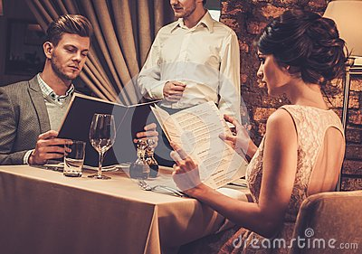 Waiter explaining the menu to wealthy couple in restaurant.
